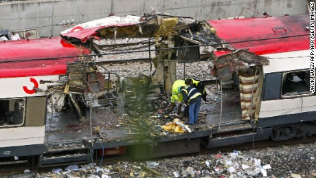 Forensic experts inspect the trains which exploded at the Atocha train station the day before, 12 March 2004 in Madrid. At least 198 people were killed and more than 1400 wounded in bomb attacks on four commuter trains, 11 March 2004.        (Photo credit should read JACK GUEZ/AFP/Getty Images)