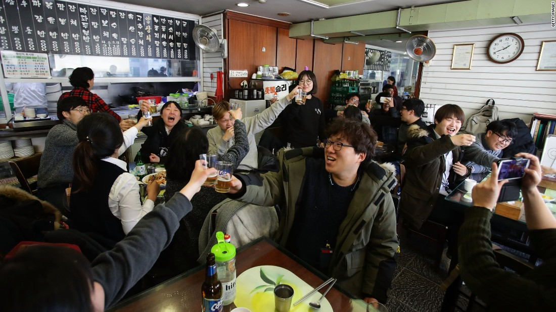 South Koreans celebrate at a restaurant after hearing the court's unanimous verdict.