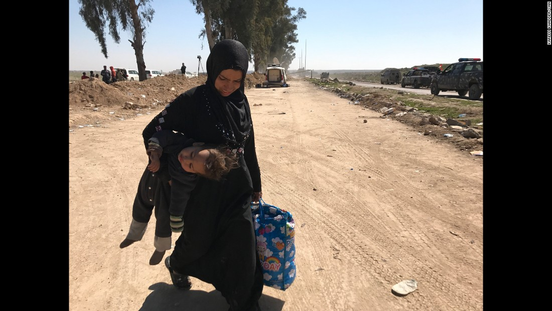 A woman carries her child in one hand and a bag of belongings in the other as she flees western Mosul's Mahata neighborhood. Many civilians are able to grab only a few belongings as they flee ISIS control.