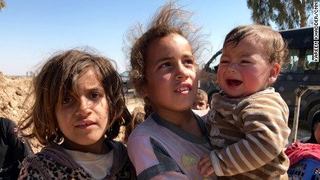 Two girls hold their little brother as they wait to be transferred to a near by refugee camp by Iraqi security forces.
