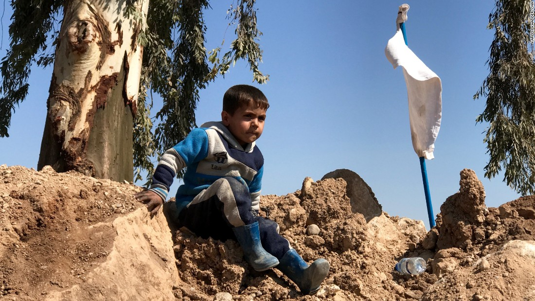 A boy climbs over a dirt mound near the Mosul airfield. White flags like the one next to him were carried by many families and civilians who fled western Mosul as fighting between Iraqi forces and ISIS raged.