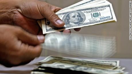 BOGOTA, COLOMBIA:  Un empleado de una casa de cambio cuenta dolares estadounidenses en Bogota el 22 de febrero de 2005. El precio del dolar en Colombia cayo al nivel de cotizacion de hace tres anos, y se cotiza hoy en 2.312 pesos, consecuencia del aumento de las exportaciones y de las remesas del exterior.          AFP PHOTO/Luis ACOSTA  (Photo credit should read LUIS ACOSTA/AFP/Getty Images)