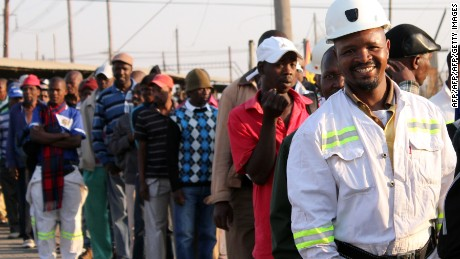 Thousands of Lonmin miners wait in line as they resume work in Marikana on September 20, 2012 after ending a deadly six-week wildcat strike as other global mining giants battled to rein in protests. Workers chatted loudly as the queue shuffled to the turnstile entrance for the 07:00 am (0500 GMT) shift at the mine's Rowland shaft, where they are to undergo medical checkups and orientation before going underground in a few days. AFP PHOTO / Cynthia Matonhodze        (Photo credit should read CYNTHIA MATONHODZE/AFP/GettyImages)