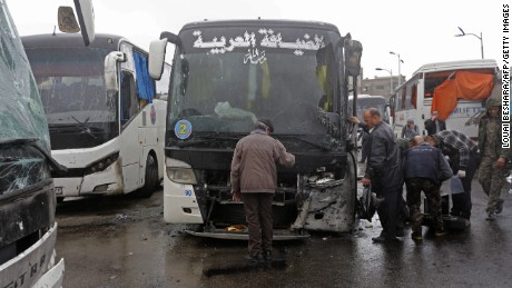 Syrian security forces, forensics and locals gather at the scene of a bombing following twin attacks targeting Shiite pilgrims in Damascus' Old City on March 11, 2017. A roadside bomb detonated as a bus passed and a suicide bomber blew himself up in the Bab al-Saghir area, which houses several Shiite mausoleums that draw pilgrims from around the world, the Syrian Observatory for Human Rights said.