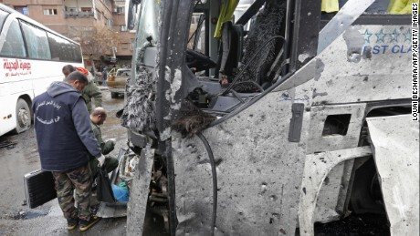 Syrian forensics examine a bus at the scene of a bombing following twin attacks targeting Shiite pilgrims in Damascus' Old City on March 11, 2017. A roadside bomb detonated as a bus passed and a suicide bomber blew himself up in the Bab al-Saghir area, which houses several Shiite mausoleums that draw pilgrims from around the world, the Syrian Observatory for Human Rights said.