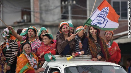 Supporters of India's Congress wave their flags as they celebrate their candidate's win in state assembly elections in Imphal on March 11.