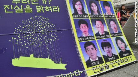 A woman (back R) walks past a placard showing portraits of missing people from South Korea's Sewol ferry disaster at Gwanghwamun Square where relatives of the victims are camped for a sit-down in Seoul on June 16, 2016.  South Korea said on June 16 it would resume salvage operations on the Sewol ferry next week, but underlined the enormous challenges posed by raising the vessel that sank in 2014 with massive loss of life. / AFP / JUNG YEON-JE        (Photo credit should read JUNG YEON-JE/AFP/Getty Images)