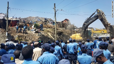 Police officers secure the scene after the landslide at the landfill, as excavators aid rescue efforts on the outskirts of Addis Ababa on Sunday, March 12, 2017.