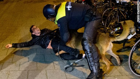 A Dutch riot police officer tries to get his dog to let go of a man during a demonstration at the Turkish consulate in Rotterdam Sunday.