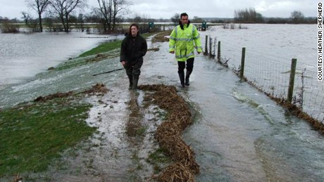 Shepherd walks with a colleague along the earth bund that should protect her village from flooding.