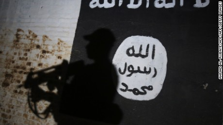 TOPSHOT - A member of the Iraqi forces walks past a mural bearing the logo of the Islamic State (IS) group in a tunnel that was reportedly used as a training centre by the jihadists, on March 1, 2017, in the village of Albu Sayf, on the southern outskirts of Mosul. Iraqi forces launched a major push on February 19 to recapture the west of Mosul from the Islamic State jihadist group, retaking the airport and then advancing north. / AFP PHOTO / AHMAD AL-RUBAYE        (Photo credit should read AHMAD AL-RUBAYE/AFP/Getty Images)