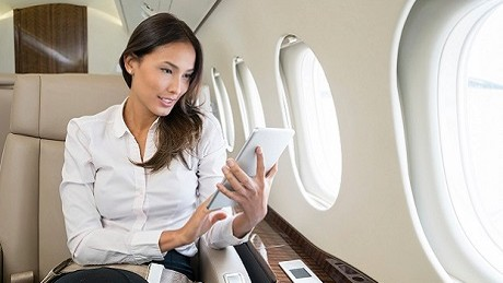 Business woman traveling and enjoying onboard entertainment on her tablet computer