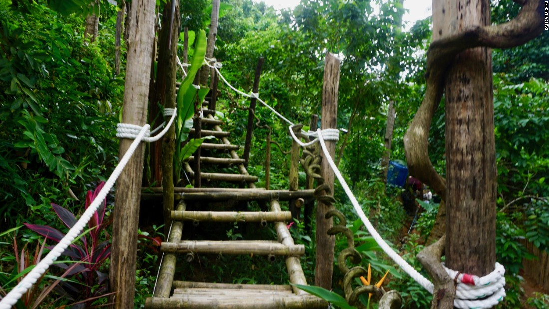 <strong>Forest trek:</strong> Follow the signs on a trek through the forest. Finally, a stairwell leads travelers up a lush mountainside where contemporary tents are visible between the tree branches.