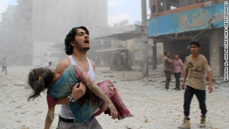 A man carries a young girl who was injured on June 3, 2014 in Kallaseh district in the northern city of Aleppo.