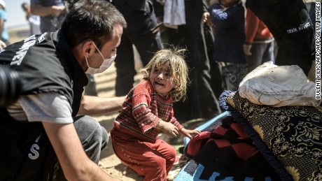 A Syrian Kurdish child cries as Turkish police search their bags after they crossed the border between Syria and Turkey at the southeastern town of Suruc in Sanliurfa province on September 23, 2014. The UN refugee agency warned Tuesday that as many as 400,000 people may flee to Turkey from Syria's Kurdish region to escape attacks by the Islamic State group.  AFP PHOTO / BULENT KILIC        (Photo credit should read BULENT KILIC/AFP/Getty Images)