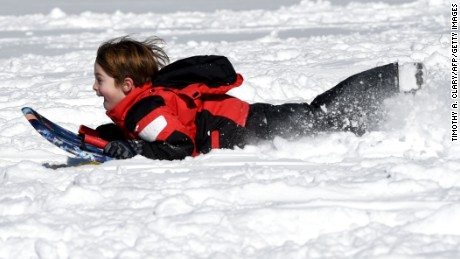 "A child goes sledding down a hill in Bruce Park in Greenwich, Connecticut on January 24, 2016. Millions of people in the eastern United States started digging out Sunday from a huge blizzard that brought New York and Washington to a standstill, but the travel woes were far from over. The storm -- dubbed ""Snowzilla"" -- killed at least 18 people after it walloped several states over 36 hours on Friday and Saturday, affecting an estimated 85 million residents who were told to stay off the roads and hunker down in doors for their own safety. / AFP / Timothy A. CLARY        (Photo credit should read TIMOTHY A. CLARY/AFP/Getty Images)"