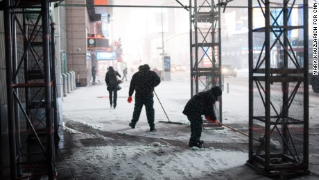 Workers shovel snow during a blizzard in Times Square in New York, NY on March 14, 2017. CREDIT: Mark Kauzlarich for CNN