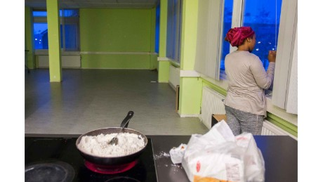 A woman from We Are Here speaks on the phone while cooking at the women's building in Amsterdam west.