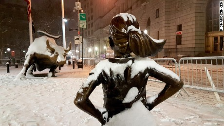 "The ""Fearless Girl"" statue faces Wall Street's charging bull sculpture in New York in the snow on March 14."