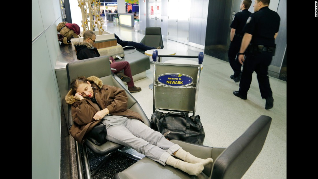 Yvonne Mouskourie makes herself comfortable after her morning flight to Florida was canceled in Newark, New Jersey.