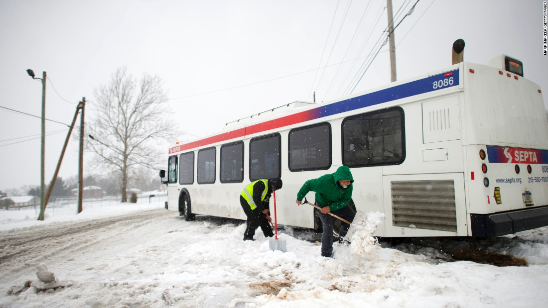 Blaine Webb helps a transit employee shovel out a bus in Spring City, Pennsylvania.