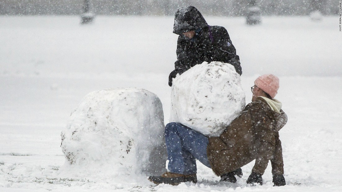 Two people work to build a snowman in Boston.