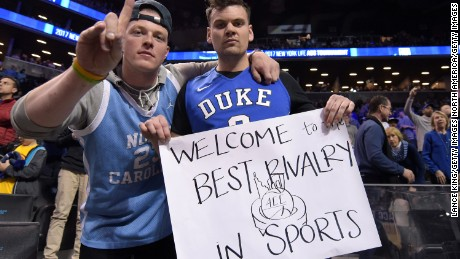 NEW YORK, NY - MARCH 10: A fan of the North Carolina Tar Heels (L) and the Duke Blue Devils pose for a photo while holding a sign referring to the Duke/UNC rivalry during the semifinals of the ACC Basketball Tournament at Barclays Center on March 10, 2017 in the Brooklyn borough of New York City. (Photo by Lance King/Getty Images)