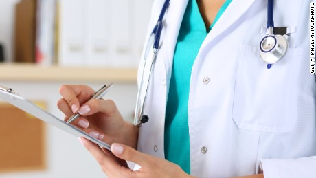 Female medicine doctor hand holding silver pen writing something on clipboard closeup. Medical care, insurance, prescription, paper work or career concept. Physician ready to examine patient and help
