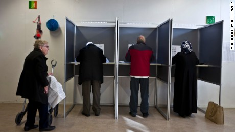 People fill out ballots during the Dutch general elections at a polling station set up in a school in Amsterdam.