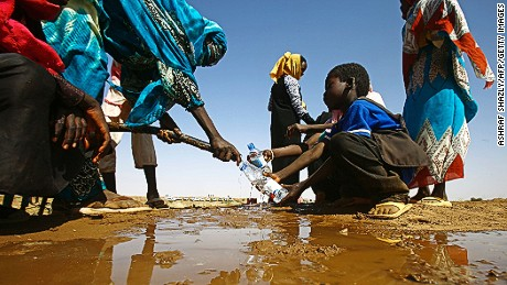 A Sudanese woman fills water bottles held by a young boy about 60 kilometres north of El-Fasher, the capital of the North Darfur state, on February 9, 2017.