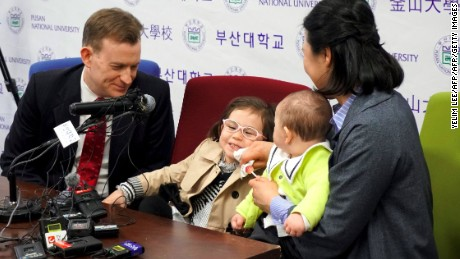 "Robert Kelly (L), an expert on East Asian affairs and a professor at South Korea's Pusan National University, his wife Kim Jung-A (R), daughter Marion (2nd L) and toddler son James (2nd R) attend a press conference at the university in Busan on March 15, 2017.   The professor who became an incidental internet sensation when his family crashed a live television interview says his wife ""deserves a medal"" for looking after him and his now-famous children. / AFP PHOTO / Yelim LEE        (Photo credit should read YELIM LEE/AFP/Getty Images)"