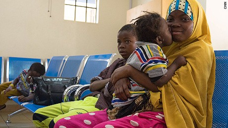 Asha gives her sister Zeinab a kiss while the family waits for medical screenings in Nairobi.