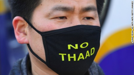 "A South Korean protester wears a black mask reading ""No THAAD"" during a rally against the planned deployment of the US-built Terminal High Altitude Area Defense (THAAD) anti-ballistic missile system, outside the Defence Ministry in Seoul on February 28, 2017. Residents living near a South Korean golf course on February 28 sued to stop it becoming the site of a controversial US missile system loathed by Beijing, their lawyers said as Chinese media poured scorn on the plan. / AFP / JUNG Yeon-Je        (Photo credit should read JUNG YEON-JE/AFP/Getty Images)"