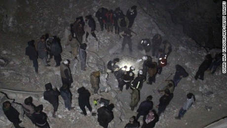 Syria Civil Defense volunteers dig through rubble after a reported airstrike Thursday on al-Jena, Syria.