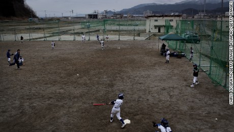 RIKUZENTAKATA, JAPAN - MARCH 10:  Members of the Takata boys baseball club practice at the Takata Elementary School field on March 10, 2012 in Rikuzentakata, Japan. The schools field was damaged by the tsunami and the club was only able to start training again in May of 2011. On the eve of the one year anniversary of the Tohoku earthquake and tsunami the effected areas have been inundated with families, friends and relatives, the limited amount of hotels in the area are full to capacity with the worlds media and people from across Japan arriving to take part in ceremonies paying tribute to the many people who lost their lives. The 9.0 magnitude strong earthquake struck offshore on March 11, 2011 at 2:46pm local time, triggering a tsunami wave of up to ten meters which engulfed large parts of north-eastern Japan and also damaged the Fukushima nuclear plant, causing the worst nuclear crisis in decades. The number of dead and missing amounted to over 25,000 people.  (Photo by Chris McGrath/Getty Images)