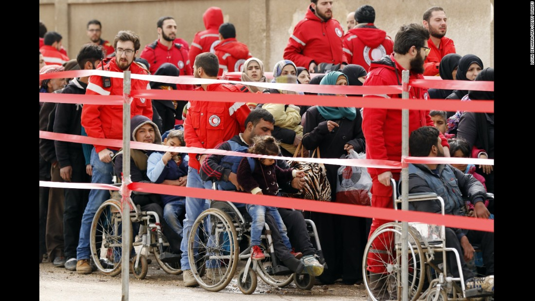 People line up to evacuate rebel-held Al-Waer neighborhood of Homs.