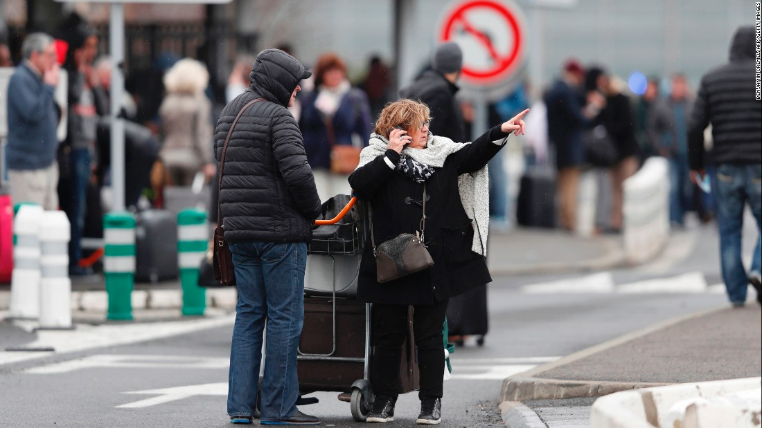 A woman talks on her cell phone as travelers evacuate Paris' Orly airport.