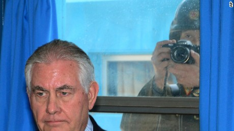 A North Korean soldier, right, tries to take a photograph through a window while US Secretary of State Rex Tillerson visits the DMZ.