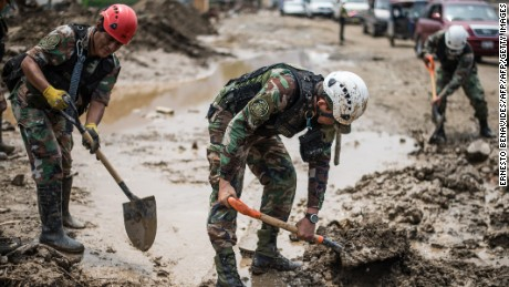 Members of the Peruvian police help clean up the mud and debris left by flash floods in Huachipa district, east of Lima, on March 19, 2017. El Nino-fuelled flash floods and landslides hit parts of Lima, where most of the water distribution systems have collapsed due to unusual heavy seasonal downpours and people are facing drinking water shortages. / AFP PHOTO / ERNESTO BENAVIDES        (Photo credit should read ERNESTO BENAVIDES/AFP/Getty Images)