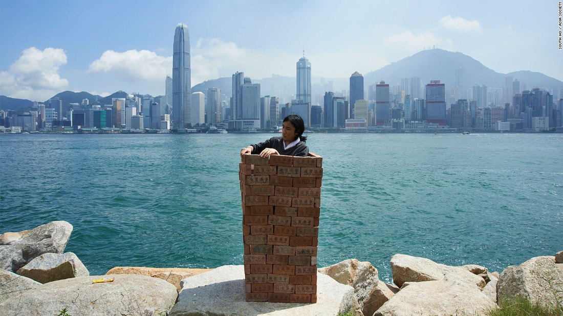 "In this iconic performance artist South Ho stands before a sparkling Victoria Harbour while building a phone booth-sized wall around himself, brick by brick. As curator Chan notes, ""There have been lots of voices saying we should keep the mainland Chinese away from Hong Kong, but what if we really do that? By building walls around you, you might have trapped yourself inside too.""<br />"