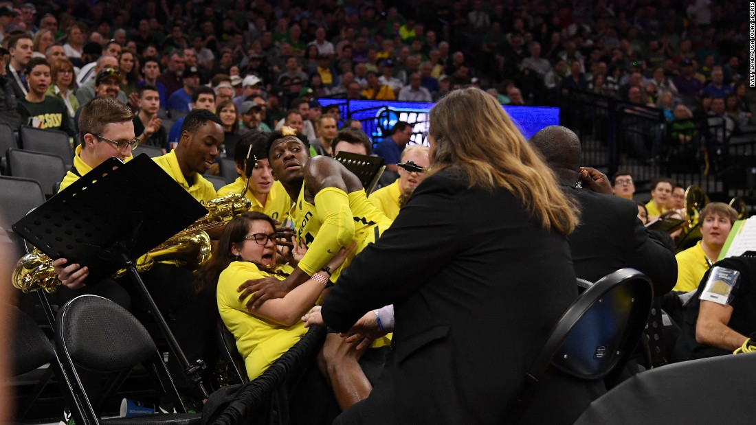 Oregon guard Dylan Ennis collides with band member Raiko Green during an NCAA Tournament game in Sacramento, California, on Friday, March 17.