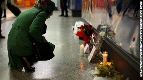 MADRID, SPAIN - MARCH 11:  A woman looks at candles, letters and flowers placed for the victims of Madrid train bombings outside a memorial monument at Atocha  railway station during the 10th anniversary on March 11, 2014 in Madrid, Spain. The worst ever terrorist attack to happen in Spain killed 192 people and injured another 1,857, after devices exploded in four commuter trains heading to Atocha Railway Station in the early hours of March 11, 2004. Many of those affected are now suffering with financial problems. Former Spanish Prime Minister Jose Maria Aznar and his government supported that the attack was made by ETA but the judicial investigation dismounted this theory.  (Photo by Pablo Blazquez Dominguez/Getty Images)
