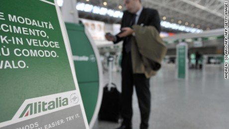 "A passenger speaks on his mobile phone near an automatic check-in machine of Italian airline Alitalia on the 10th day of a strike by pilots and flight crew protesting a takeover deal on November 19, 2008 at Rome's Fiumicino airport. Italian Prime Minister Silvio Berlusconi  said the day before that Rome will look ""very favourably"" on a mooted collaboration between stricken Italian carrier Alitalia and German airline Lufthansa. AFP PHOTO / ANDREAS SOLARO (Photo credit should read ANDREAS SOLARO/AFP/Getty Images)"