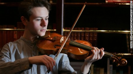 "Guildhall School of Music and Drama student Samuel Staples poses with the ""ExCroall; McEwen"" violin made by Antonio Stradivari in 1684."