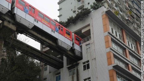CHONGQING, CHINA - MARCH 18: A rubber-wheel light-rail train passes through a 19-floor building which hosts Lizibai Station on March 18, 2017 in Chongqing, China. 