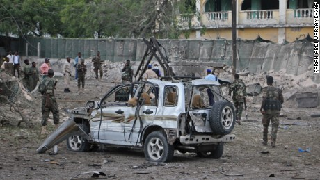 Somali soldiers stand near the wreckage of a car bomb attack in Mogadishu.