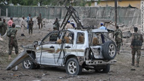 Somali soldiers stand near the wreckage of a car bomb attack that targeted a checkpoint in Mogadishu, Somalia Tuesday, March 21, 2017. The car bomb exploded Tuesday at a military checkpoint near Somalia's presidential palace in the capital, after soldiers tried to stop the car and the bomber tried to speed through the checkpoint, killing a number of people, police said. (AP Photo/Farah Abdi Warsameh)