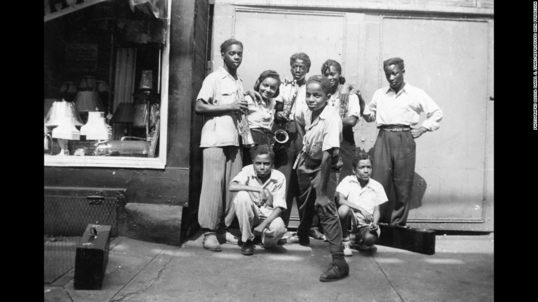 "Some of Fitzpatrick's friends pose near a lamp shop. Evans had possession of his mother's scrapbook after her death, which happened 30 years ago on March 23. He said Smithsonian curators were amazed when they first saw her photos. ""You can find photos like my mother's that are 70-80 years old, but typically people don't know who's in the photos, they don't know where the photos were from,"" Evans said. ""But my mother really documented how African-Americans, for a 10-year period, adjusted to life in the North coming from the rural South. And it showed how communities were formed."""