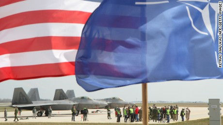 The US and The NATO flag fly in front of two US Air Force F-22 Raptor fighter aircraft at the Air Base of the Lithuanian Armed Forces in Siauliai, Lithuania, on April 27, 2016.
