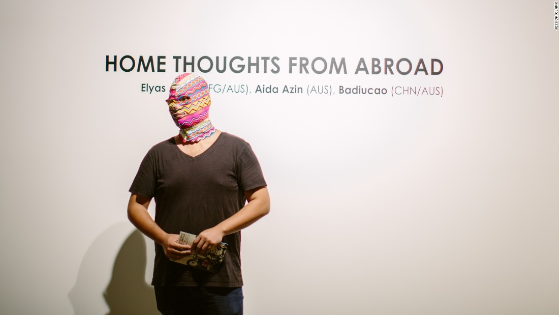 Badiucao, his face covered by a burkini-mask, discusses his work at the opening of his March 2017 show in Adelaide.